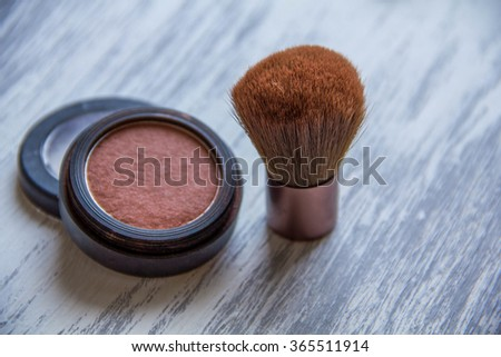 makeup brush and cosmetics, on a wooden background  - stock photo