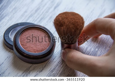 makeup brush and cosmetics, on a wooden background