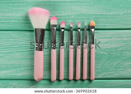 Makeup brush set on a mint wooden background - stock photo