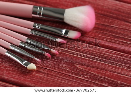 Makeup brush set on a red wooden background