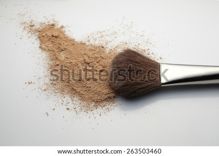 Makeup Brush with beige loose Face Powder placed horizontal on white gradient background. - stock photo
