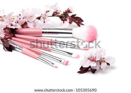 Makeup Brushes and cherries flowers on a white background - stock photo