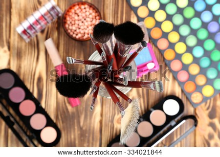 Makeup brushes and cosmetics on brown wooden table - stock photo