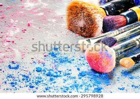 Makeup brushes and crushed eyeshadow  - stock photo
