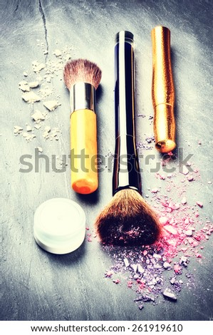 Makeup brushes and makeup products on dark background - stock photo