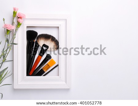 Makeup Brushes in a white frame with flowers on a white background
