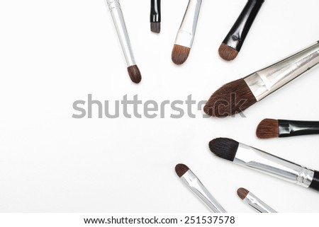 makeup brushes of different size and color white background - stock photo