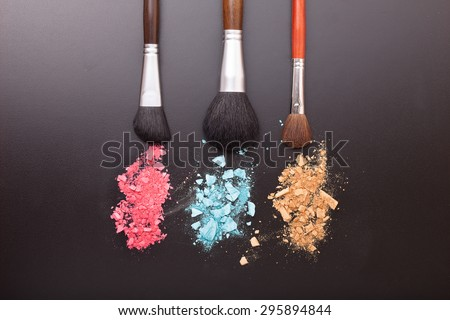 Makeup brushes on background with colorful powder. Crushed eyeshadow on black background. Abstract  background  - stock photo