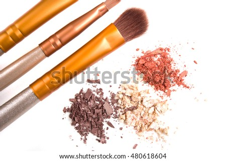 Makeup brushes set and loose eyeshadows isolated