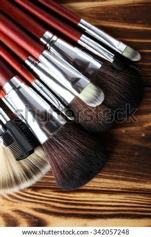 Makeup brushes set on a brown wooden background - stock photo