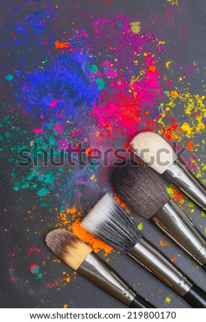 Makeup brushes with colorful powder. Beauty concept - stock photo