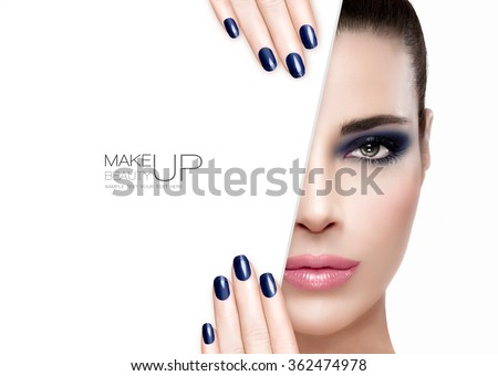 Makeup Concept. Beautiful fashion model girl with smoky eye in blue to match her manicured nails, foundation on a faultless skin with trendy pink lipstick, half face with a white card template. - stock photo