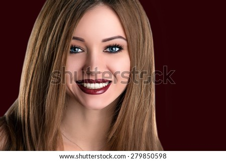 Makeup Concept. Beauty Toothy Smile and Red Wine Lips. Burgundy Lipstick. Blue Eyes with Long Lashes. Beautiful Female Face Smiling Young Woman  Portrait over Black Background. - stock photo