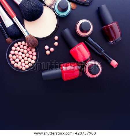 Makeup cosmetics products on dark background with copy space. Cosmetics make up artist objects: lipstick, eye shadows, eyeliner, concealer, nail polish, powder, tools for make-up. Selective focus - stock photo