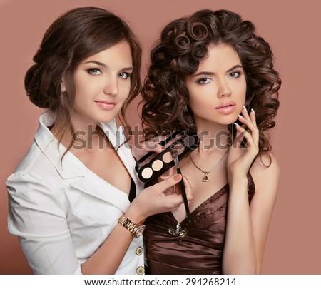 Makeup. Hairstyle. Curly hair. beauty salon. Beautiful fashion model.  Makeup stylist artist applies eye shadow. Perfect make-up - stock photo