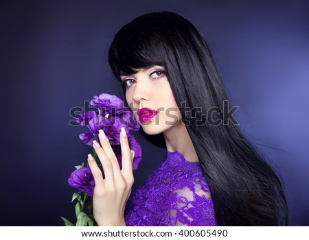 Makeup. Long hair. Beautiful brunette woman with purple flowers, manicured nails, healthy black hairstyle. Beauty studio portrait. - stock photo