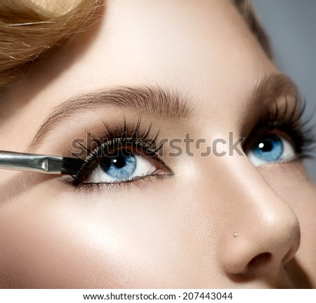 Makeup. Make-up Applying closeup. Eyeliner. Cosmetic Eyeshadows. Eyeline brush for Make up. Beauty Girl with Perfect Skin. Eyelashes. Blue eyes. Makeover  - stock photo