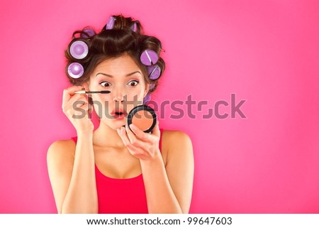 Makeup mascara woman with hair rollers getting ready looking in pocket mirror. Funny image of beautiful trendy young mixed race asian caucasian female fashion model putting makeup on pink background.