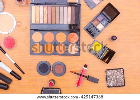 Makeup Palettes and Cosmetics Professional Brushes on a Wooden Background / Makeup Palettes and Cosmetics Professional Brushes / Makeup Splash - stock photo
