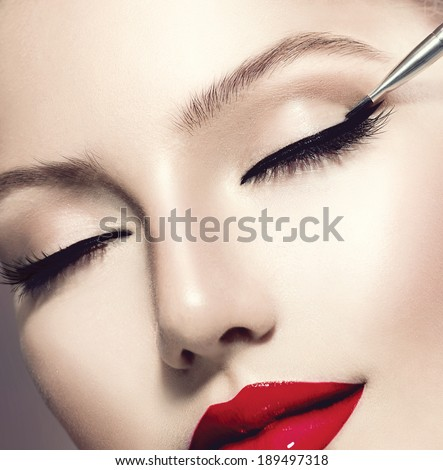 Makeup. Perfect Make-up Applying closeup. Eyeliner. Cosmetic Eyeshadows. Eyeline brush for Make up. Beauty Girl with Perfect Skin. Eyelashes. Red Lipstick. Makeover - stock photo