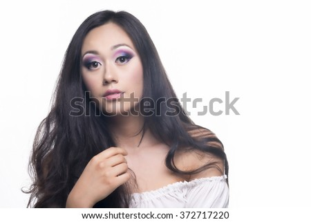 Makeup portrait of a model with long and black hair isolated over white background