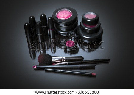 Makeup products on dark background with reflection. Copy space for your text. Studio shot. Horizontal picture - stock photo