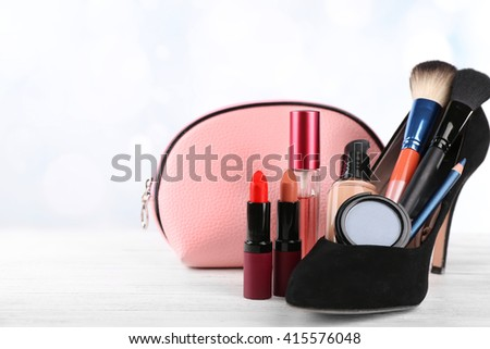 Makeup set with black woman's shoe, beautician, brushes and cosmetics on white background - stock photo