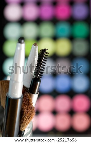 Makeup set with colorful eye shadows as background.