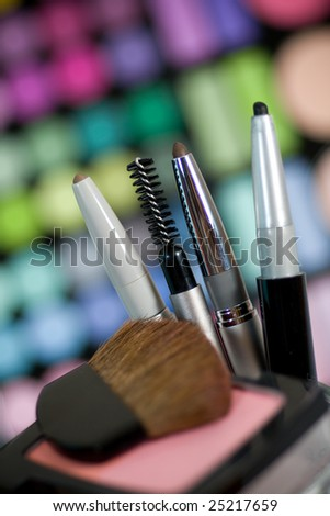 Makeup set with colorful eye shadows as background