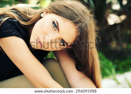 Makeup. Sexy beautiful young woman posing in palm leaves outdoors. Portrait of beautiful caucasian stylish young woman with smoky eyes. Vogue style fashion photo. - stock photo