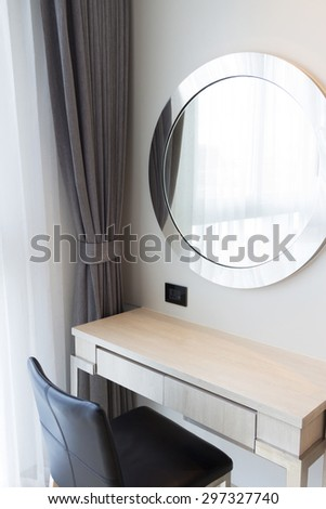 makeup table and oval mirror in bedroom. - stock photo