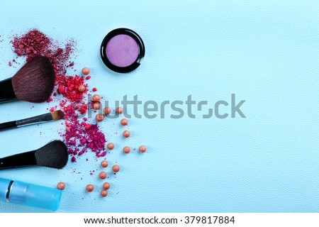 Makeup tools and cosmetics on blue background - stock photo