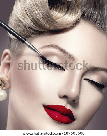 Makeup. Vintage style Make-up Applying closeup. Eyeliner. Retro styled Woman. Eyeline brush for Make up. Beauty Girl with Perfect Skin. Eyelashes. Red Lipstick. Makeover - stock photo