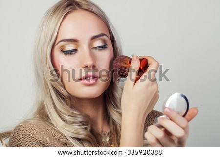 Makeup. Woman applying cosmetics with mirror - stock photo