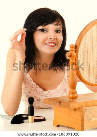 makeup, young lady applying eye mascara, white background - stock photo