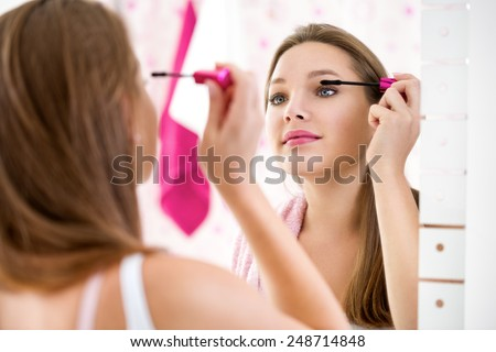 Makeup young  woman putting lipstick wearing hair rollers getting ready for going out. - stock photo