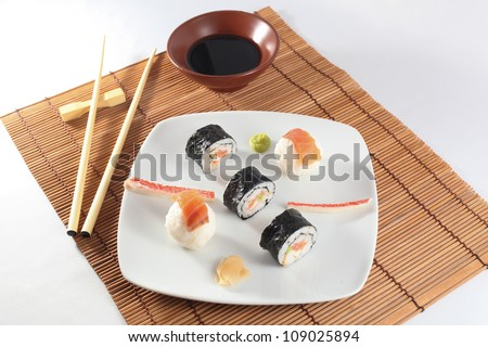 Maki delicious sushi menu with wasabi, soy sauce and chopsticks on white plate - stock photo