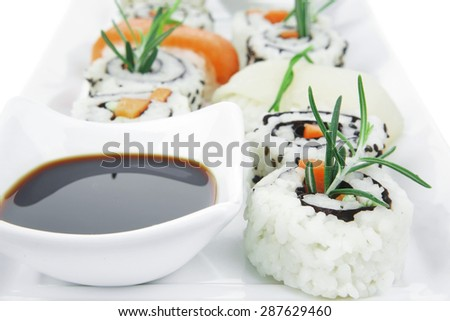 Maki Rolls and California rolls made of fresh raw Salmon, Tuna and Eel with Cream Cheese and Avocado . Isolated over white background . on long white plate . Maki Sushi and Nigiri - stock photo