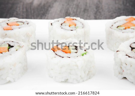 Maki Sushi - California Roll made of Fresh raw Salmon, Cream Cheese and Avocado inside. Served with wasabi . over black table . on square white plate - stock photo