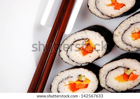 Maki Sushi : Maki Rolls and California rolls made of fresh raw Salmon, Tuna and Eel . on black dish with red and blue crabs .