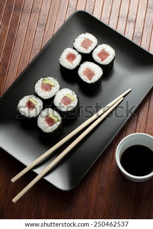 maki sushi on black plate with chopsticks