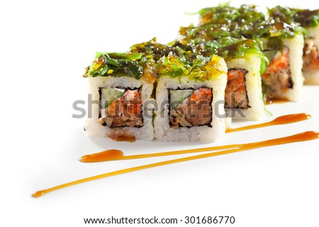 Maki Sushi - Roll with Fried Salmon, Cucumber and Cheese inside. Topped with Chuka Seaweed - stock photo