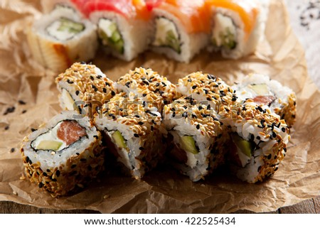 Maki Sushi - Roll with Smoked Salmon, Cream Cheese and Avocado inside. Sesame outside - stock photo