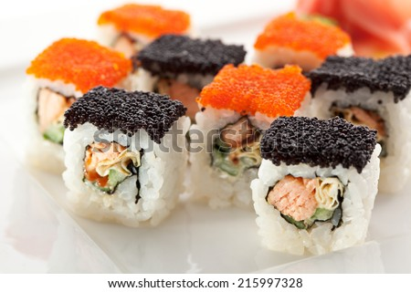Maki Sushi with Salmon, Cucumber and Tamago inside. Topped with Tobiko - stock photo