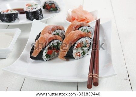 maki uramaki and onigiri sushi rolls with ginger and japan vinegar and sticks on plates over white wooden table - stock photo