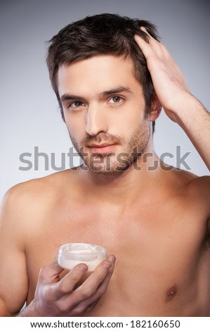 Making a charming style. Handsome young shirtless man touching his hair with hand while holding a container with gel and isolated on grey background - stock photo