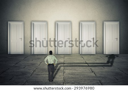 Making a choice opportunity concept. Businessman facing group of career opportunities with his cast shadow preferring or choosing one door entrance symbol for odds of success. - stock photo