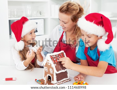 Making a gingerbread cookie house with the kids at christmas time - stock photo