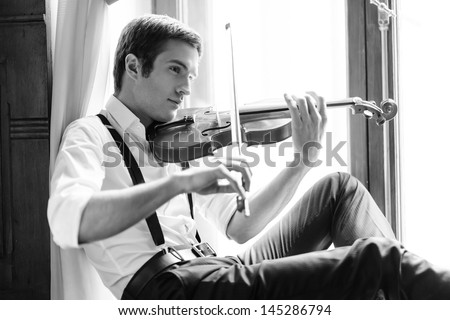 Making a magic sound. Handsome young men sitting on the windowsill and playing the violin - stock photo