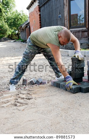 Making a pavement.Mason is building pavement. Hands in gloves lays layers of bricks.